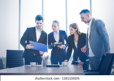 Business people standing and brainstorming in workshop meeting room with sunlight background