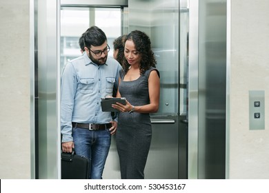 Business people standing in elevator and discussing data on tablet computer
