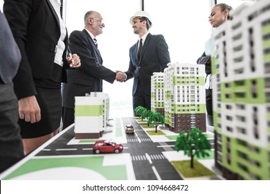 Business people standing near residential quarter houses models and shaking hands, meeting of architects and investors