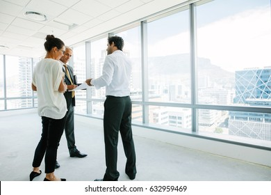 Business people standing at new office space discussing with estate broker. Real estate agent talking with potential clients inside an empty office space.