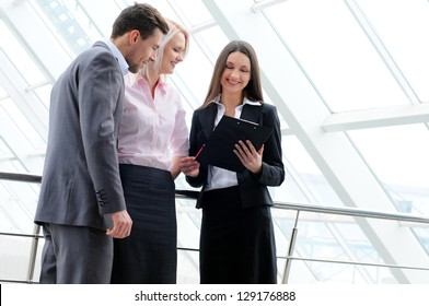 Business People standing in the office and looking at a tablet