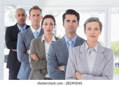 Business people standing in a row arms crossed in the office