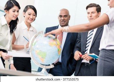Business people in Strategy meeting discussing new markets looking at a globe