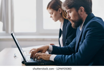 Business people in suits are sitting at the table, near the window and typing text on a laptop