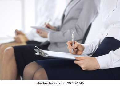Business people taking part at conference or training at office, close-up. Women sitting on chairs and making notes like at queue or meeting