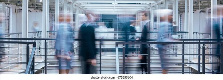 Business people talking in office corridor, industrial interior, panorama