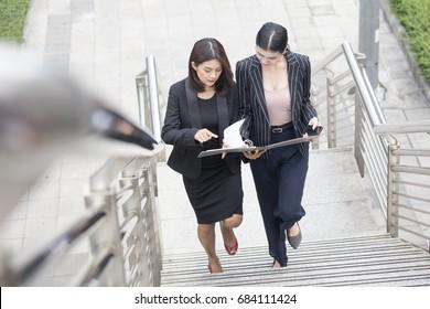 Geschäftsleute, die beim Gehen für Geschäftspläne sprechen. Frauenwanderkonzept. 20-30 Jahre alt.