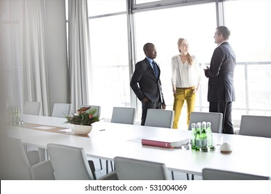 Business people talking while standing by conference table in office
