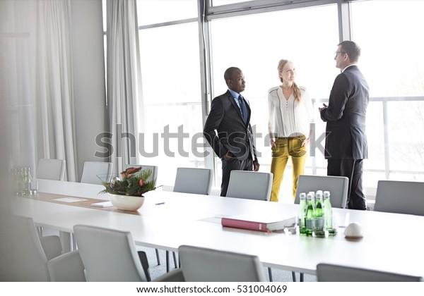 Ludzie biznesu rozmawiają stojąc przy stole konferencyjnym w biurze