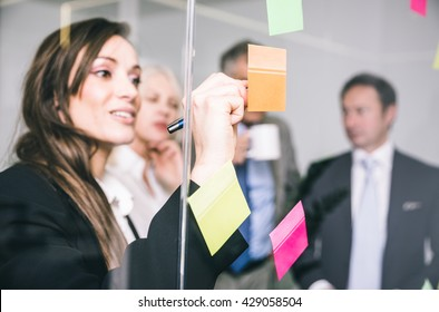 Business people talking and writing notes on the post it cards