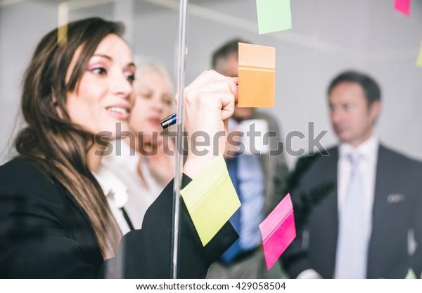 Geschäftsleute, die sich unterhalten und Notizen auf den Postkarten schreiben