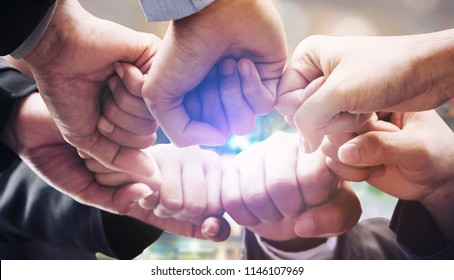 Business people team joining hands showing teamwork, collaboration and unity.