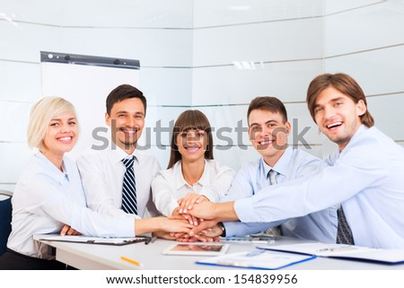 Business people team at office meeting, group of smile businesspeople leader hold pile of hands putting on top of each other on desk, concept of collaboration, working together cooperation