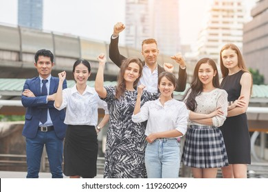 Business People Team Success Achievement Arm Raised Togetherness Happiness company with happy workers Outside Office. Group friends economists, students, financiers, lawyers or Volunteer on city