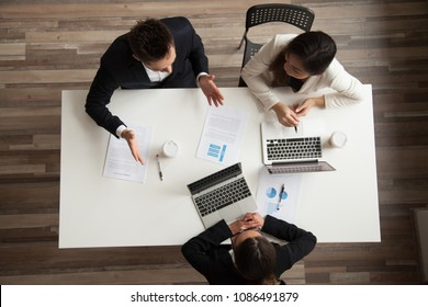 Business people team talking working together at meeting, diverse colleagues office workers discussing planning project or preparing report with laptops papers, teamwork concept, top view from above