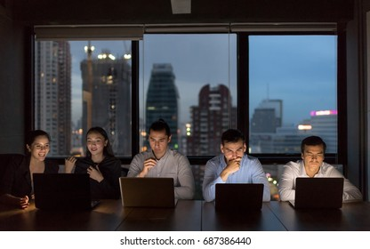 Business people team working late night in low light from laptop screen with cityscape blurred background.Overtime hours concept.
