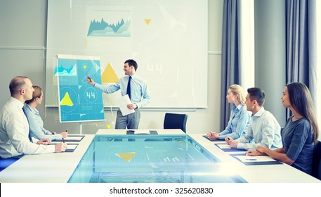 business, people and teamwork concept - group of smiling businesspeople with virtual charts projection meeting on presentation in office