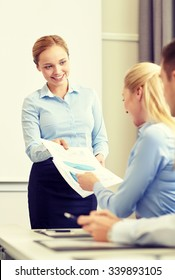 business, people and teamwork concept - smiling woman giving papers to group of businessmen in office