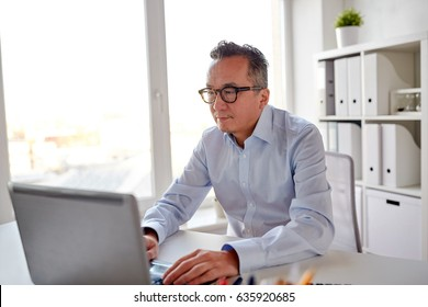 business, people and technology concept - businessman in eyeglasses with laptop computer office
