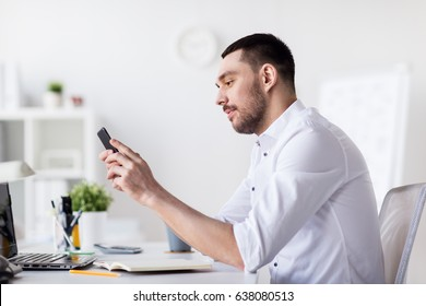 business, people and technology concept - businessman with smartphone and notebook at office