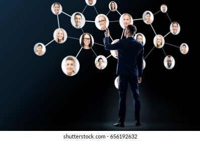 business, people and technology concept - businessman in suit with virtual icons of corporate network over black background