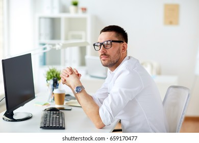 business, people and technology concept - businessman in glasses sitting at office computer and thinking