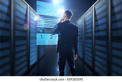 business, people and technology concept - businessman in suit with charts on virtual screen over server room background