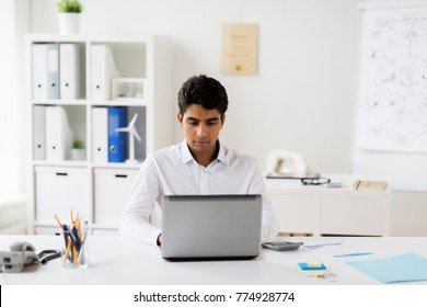 business, people and technology concept - businessman with laptop computer and papers working at office