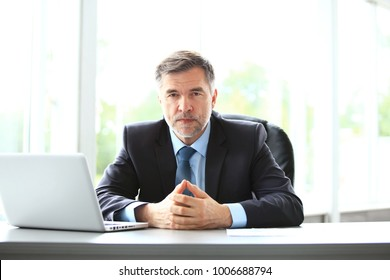 business, people and technology concept - happy smiling mature businessman with laptop computer office