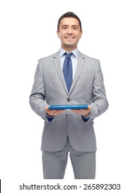 business, people and technology concept - happy smiling businessman in suit holding tablet pc computer