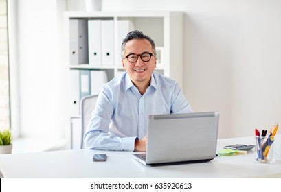 business, people and technology concept - happy smiling businessman in eyeglasses with laptop computer office