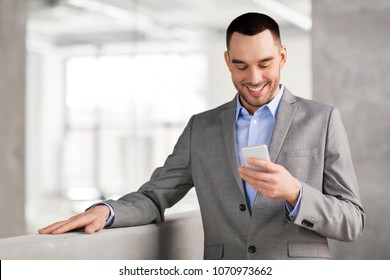 business people, technology and corporate concept - smiling businessman with smarphone at office