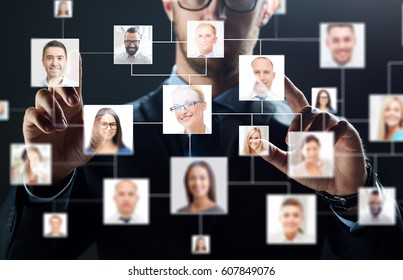business, people, technology, hiring and employment concept - close up of businessman in suit working with contact icons over black background