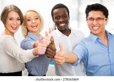 Business people with thumbs up and smilingin in office