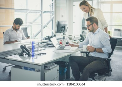 Business people together in office. Colleague reading document. African business man typing on smart phone.