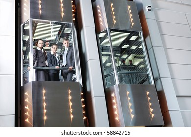 Business people traveling in the elevator looking down