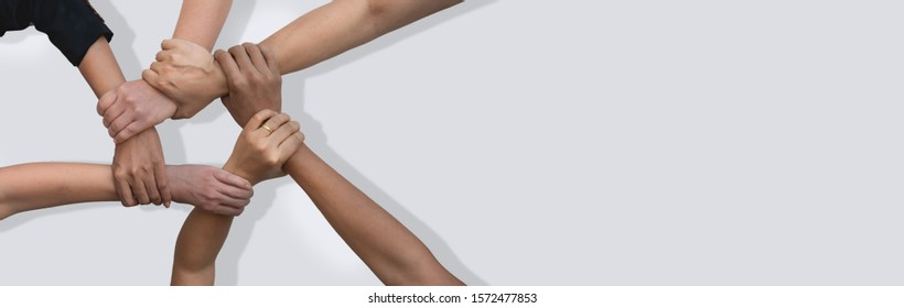 Business people united hands together in teamwork on white background with copy space for header.