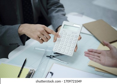 Business people using calculator in meeting