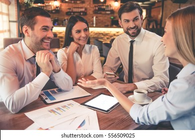 Business people are using gadgets, talking and smiling while working in cafe