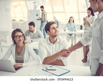 Business people are using gadgets, talking and smiling while working in office. Partners are shaking hands