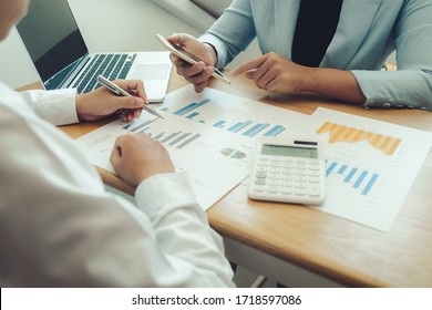 Business people is using mobile phone for analyzing sales graph and planning with another business man in the office, Business discussing and planning strategy concept.