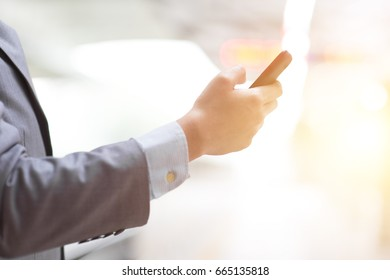 Business people using smart phone outdoors, focus on hand, bright sun flare background.