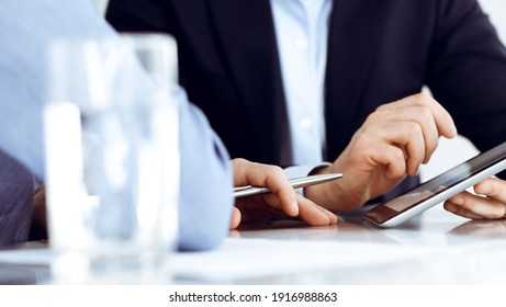 Business people using tablet computer while working together at the desk in modern office. Unknown businessman or male entrepreneur with colleague at workplace. Teamwork and partnership concept