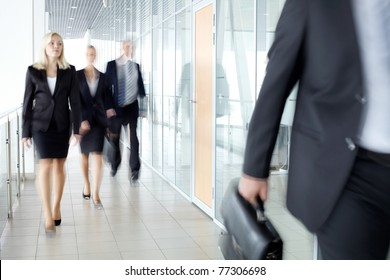 Business people walking along the office corridor