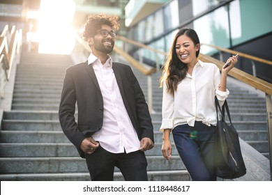 Business people walking down the stairs in the street, while talking and laughing