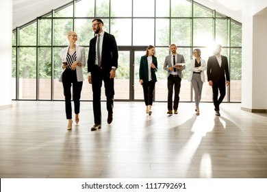 Business people walking forward and talking together at the modern office hall indoors