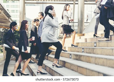 Business People Walking go to  Modern City to Working in the Office. Crowded group of people businesswoman , female in big city lifestyle with briefcase, smart phone, coffee cup. Business Concept.