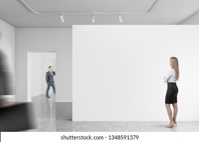 Business people walking and looking at mock up wall of modern gallery with white walls. Concept of marketing and product placement. Mock up blurred