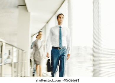 Business people walking in the office corridor, blurred motion