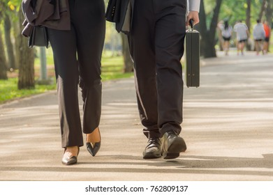 Business people walking on a concrete road Within the shady park and the fresh air. After completing the mission from the work done. To relax